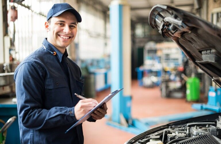 A mechanic working and smiling while checking off a list for the vehicle checkup.