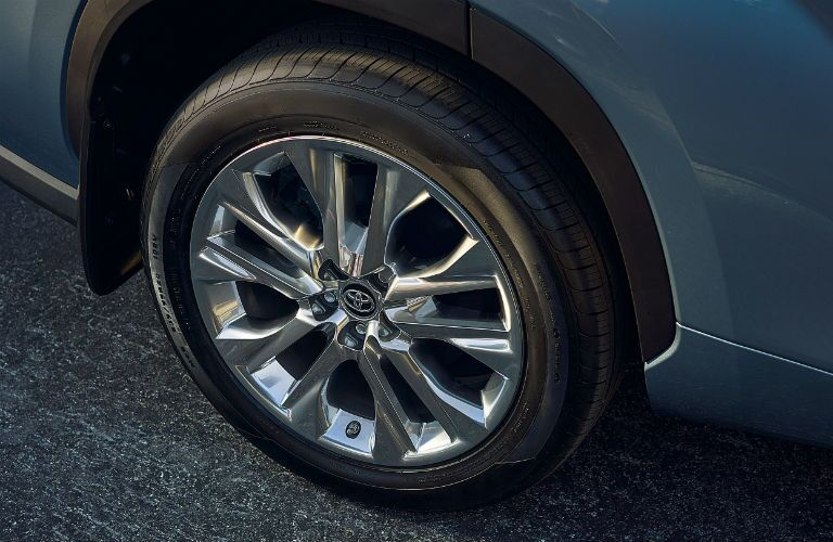 A view of a rear wheel on a blue 2021 Toyota Highlander Hybrid.