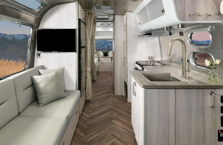 The interior view of the hallway, seating area, and kitchen in a 2021 Airstream International.