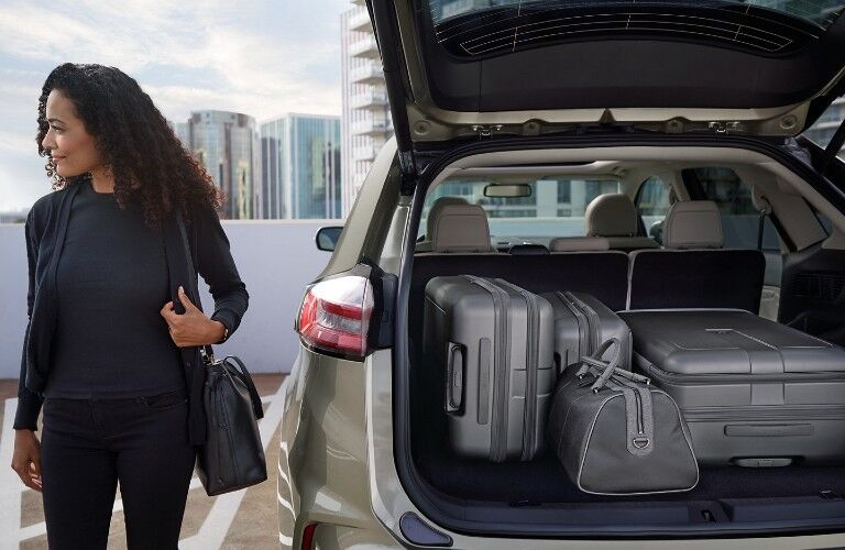 Rear angle of the 2020 Ford Edge with its liftgate open and luggage bags loaded inside and a woman standing next to it