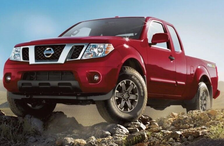 Front driver angle of a red 2019 Nissan Frontier with its front wheels resting on rocks
