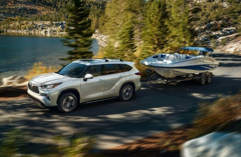 Exterior view of a white 2020 Toyota Highlander towing a boat