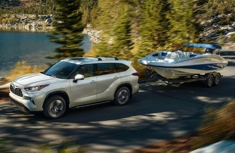 Exterior view of a silver 2021 Toyota Highlander towing a boat