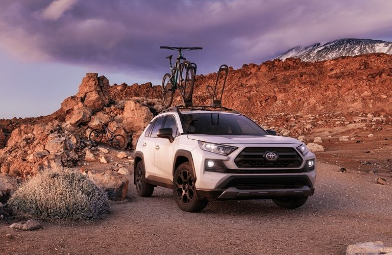 2020 Toyota RAV4 with bike on roof rack parked by mountain