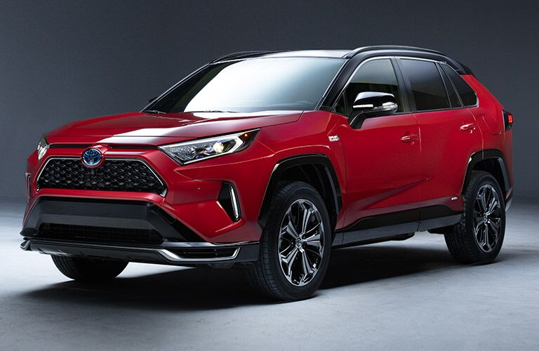 The front and side view of a red 2021 Toyota RAV4 Prime.