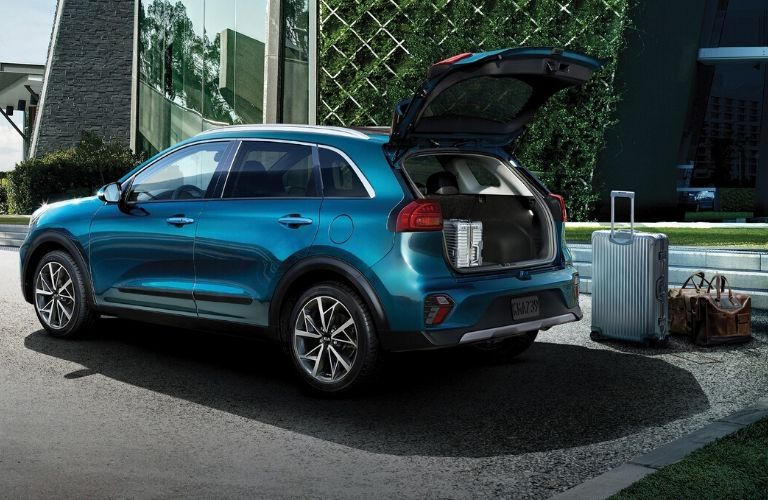 Exterior view of the rear of a blue 2020 Kia Niro with the rear hatch open