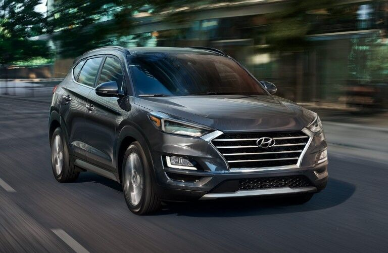 Front passenger angle of a grey 2020 Hyundai Tucson driving down a road