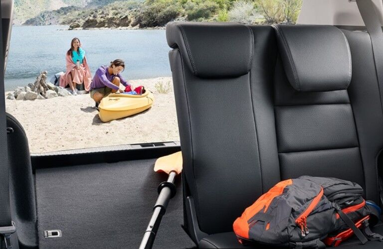 Seat in the 2019 Honda HR-V folded with a paddle inside and a couple sitting on the beach in the backgorund