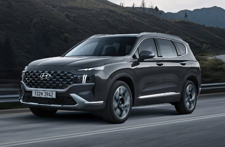 The 2021 Hyundai Santa Fe driving on a road with hills in the background