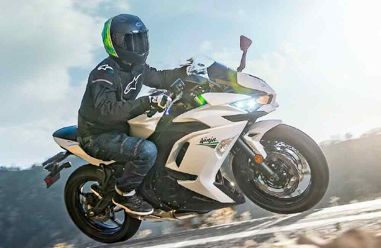 A man driving a 2020 Kawasaki Ninja 650 down the road.