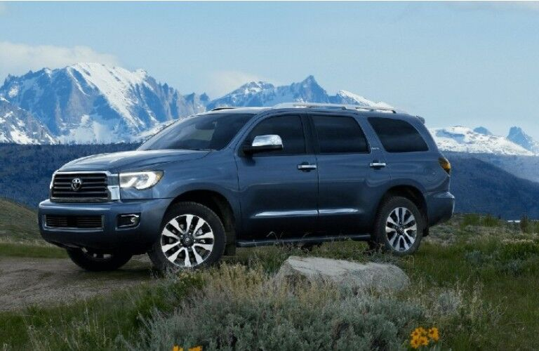A 2021 Toyota Sequoia parked on a dirt path near some grass and mountains