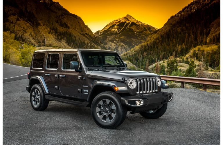 A 2021 Jeep Wrangler parked on a slab of concrete in front of a sunset and mountain range