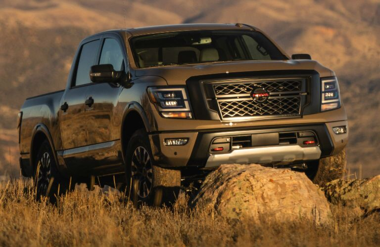 2021 Nissan TITAN parked behind a small rock