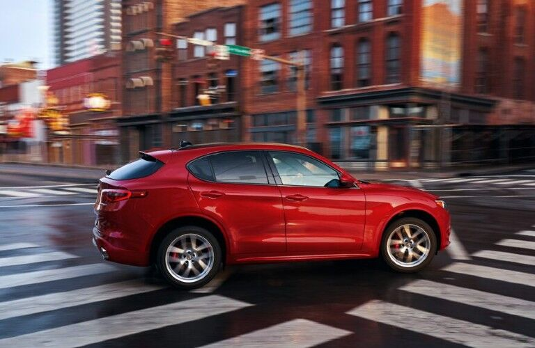 Passenger angle of a red 2020 Alfa Romeo Stelvio driving in a city