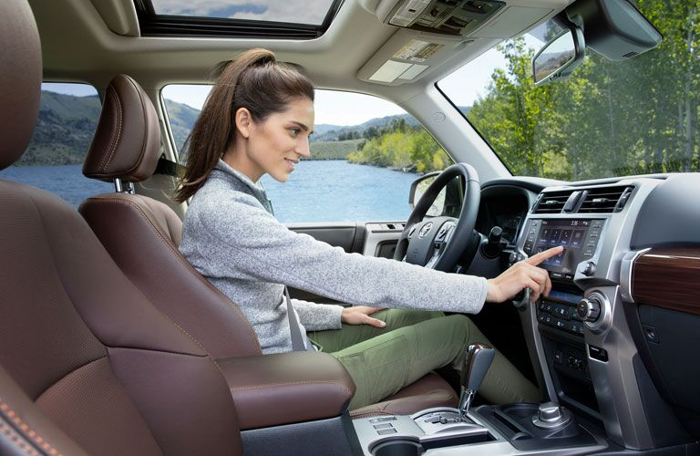 2020 Toyota 4Runner with a woman driving and operating the touchscreen