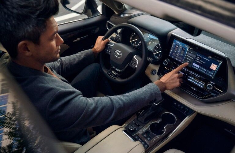 Man driving a 2021 Toyota Highlander while adjusting settings on the touchscreen