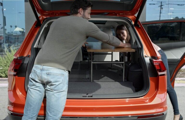 Rear angle of the liftgate opened on the 2019 Volkswagen Tiguan and a man and woman loading a table inside