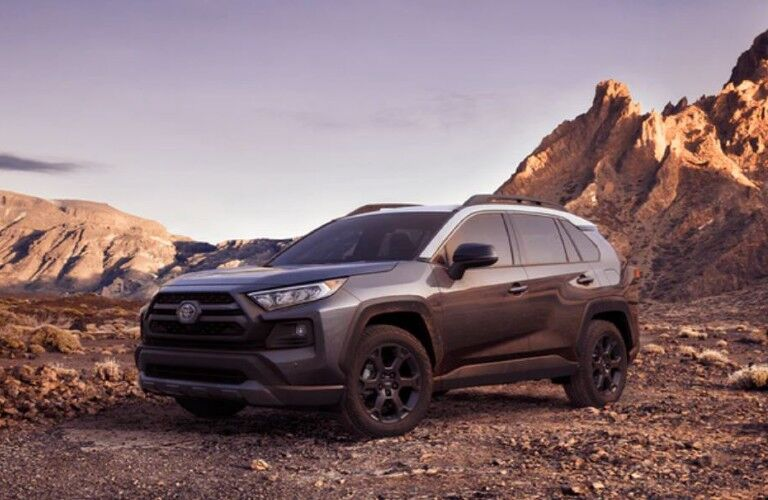 The front and side view of a black 2021 Toyota RAV4 parked on rough terrain.
