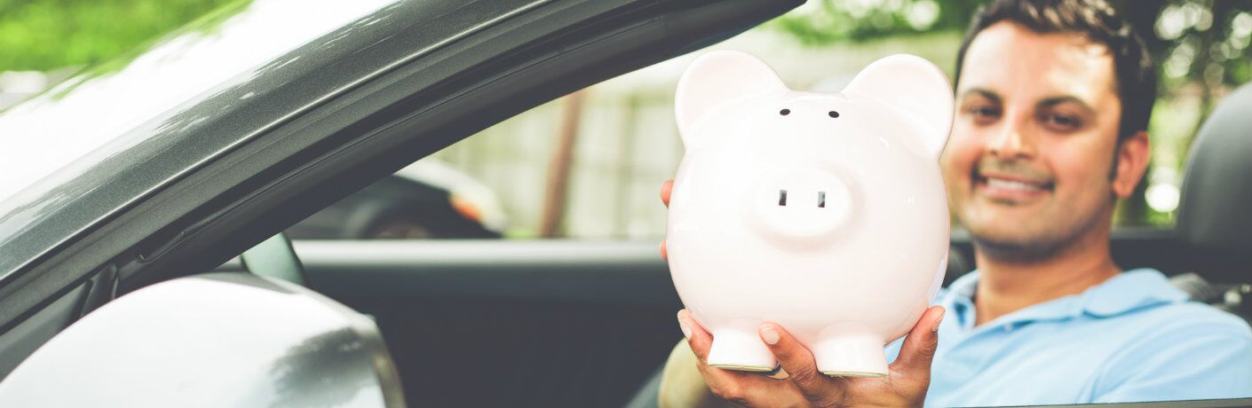 young man holding piggy bank while sitting in driver's seat of car