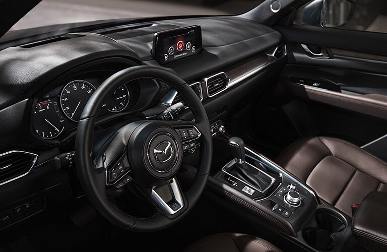 The front interior steering wheel and center console inside a 2020 Mazda CX-30.