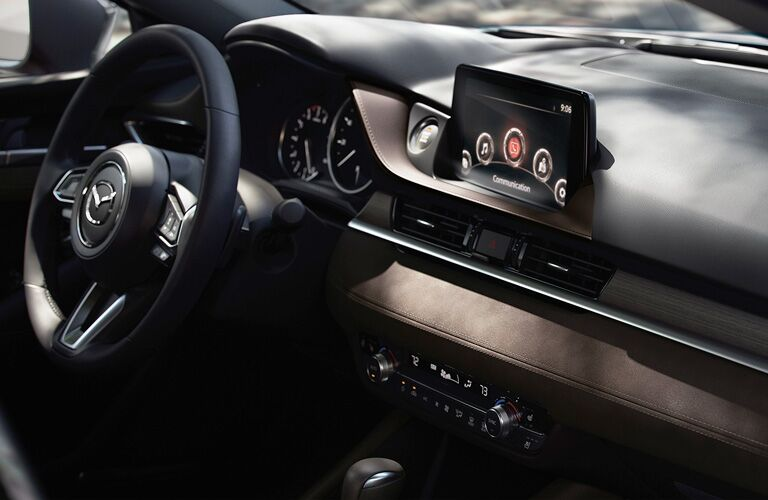 Interior view of the steering wheel and touchscreen display inside a 2020 Mazda6