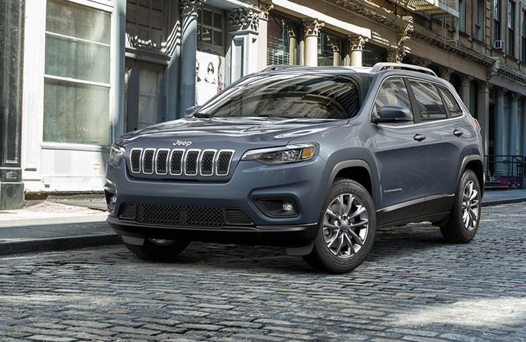 2019 Jeep Cherokee driving on a cobblestone street through a city.