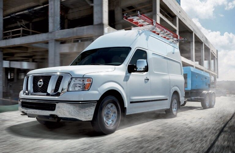 Front driver angle of a white 2020 Nissan NV2500 HD with high roof pulling equipment through a construction zone