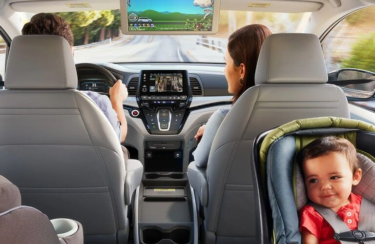 Rear angle of a couple driving in the front row with the rear entertainment system on and a baby in the back seat
