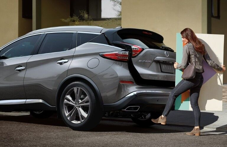 Rear driver angle of a grey 2020 Nissan Murano with a woman using the Motion Activated Liftgate while holding a large item