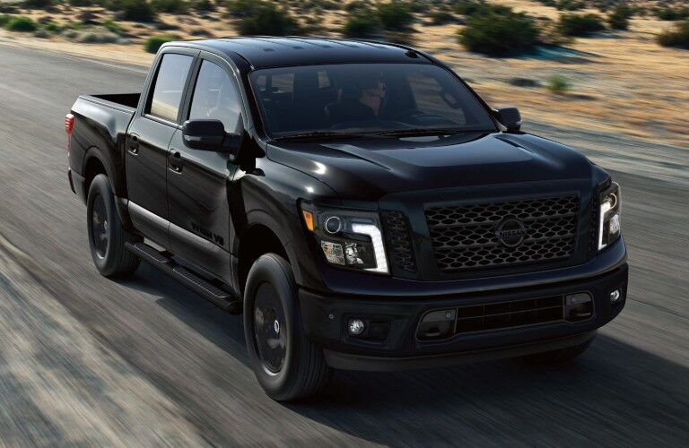 Front passenger angle of a black 2019 Nissan TITAN driving down a road