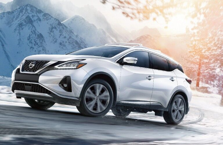 Front driver angle of a white 2020 Nissan Murano driving on a road during winter