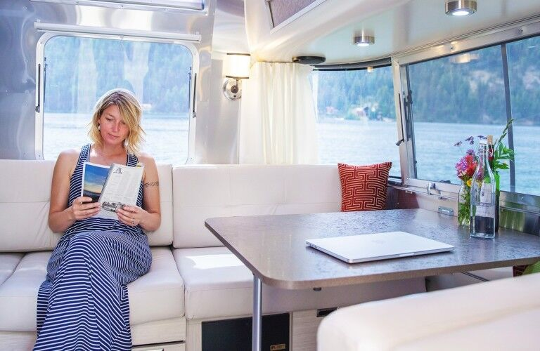 The interior view of a woman reading a magazine at the rear dining table in the 2021 Airstream International.