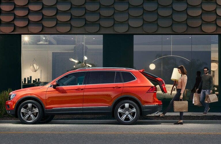 Driver angle of an orange 2019 Volkswagen Tiguan with a woman opening the liftgate with her foot