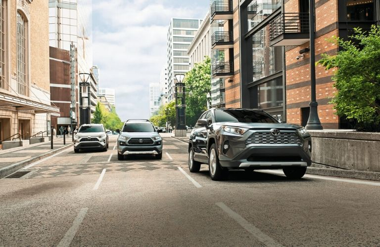 Three 2020 Toyota RAV4 models driving on the road