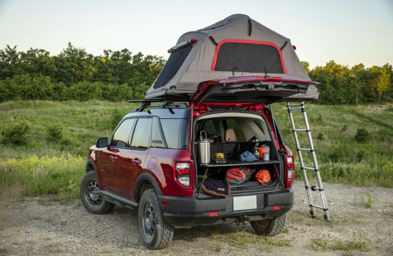 The rear image of a red 2021 Ford bronco Sport parked with an attachable tent set up on top of its roof racks.