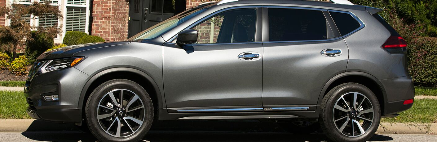 Profile view of gray 2018 Nissan Rogue parked in front of house in daytime