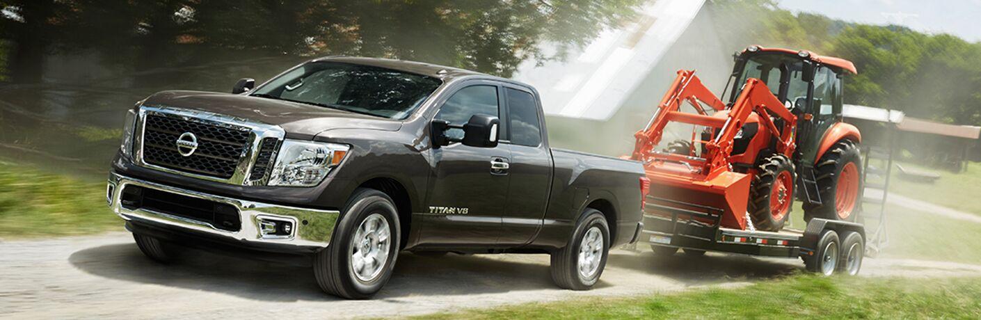 Black 2018 Nissan Titan towing trailer in daytime