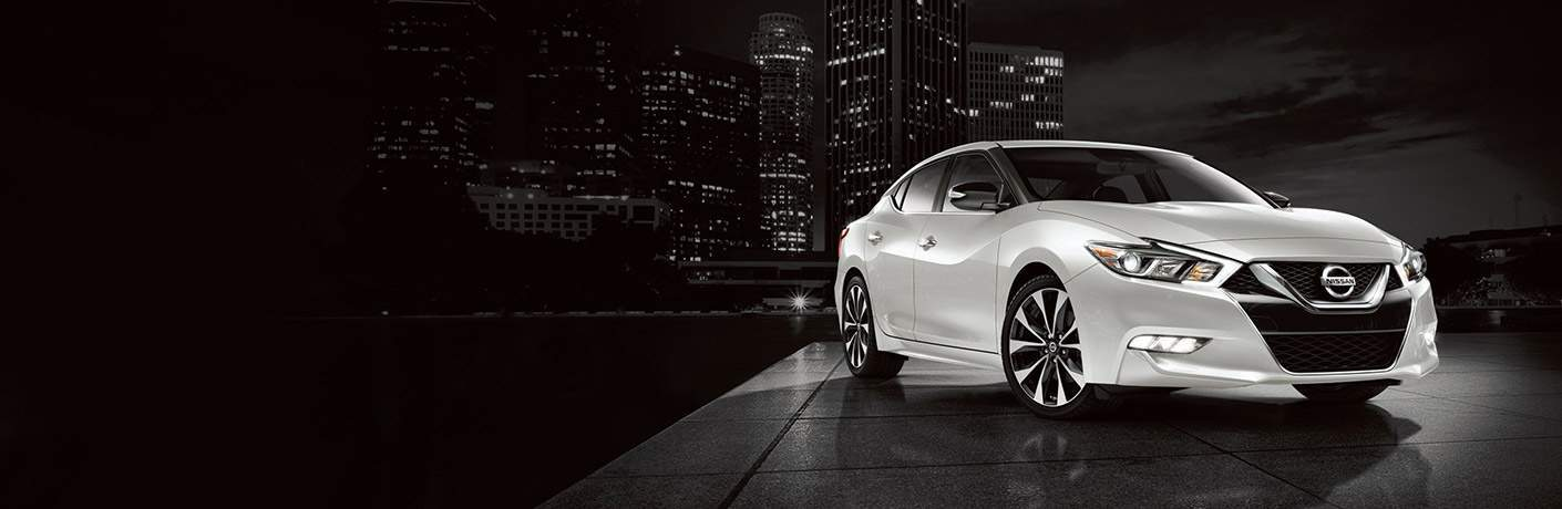 White Nissan Maxima model parked in front of city skyline view at night