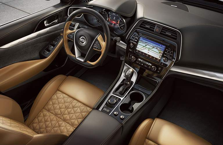 Front row of seating in 2018 Nissan Maxima with leather seats and D-shaped steering wheel prominent in view