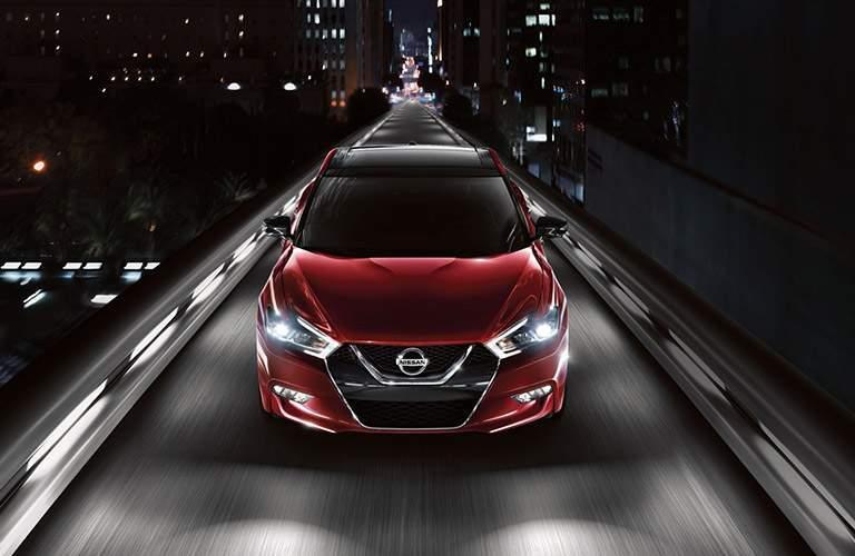 Red 2018 Nissan Maxima driving down illuminated city street at night