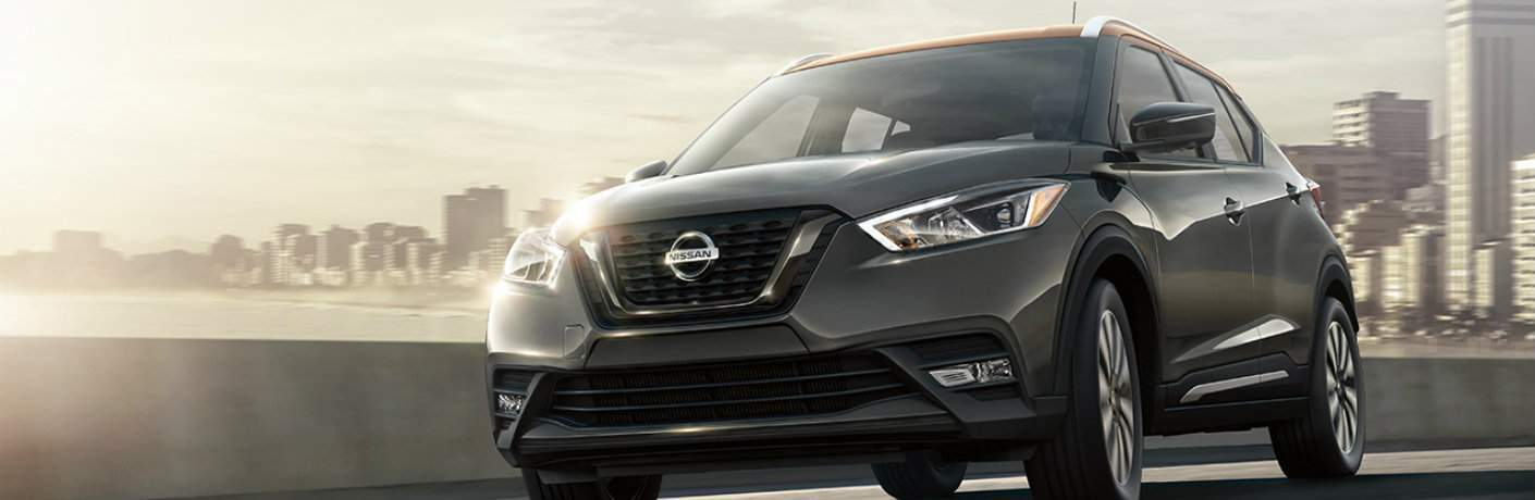 Gray and Orange 2018 Nissan Kicks model driving down road with city skyline in background
