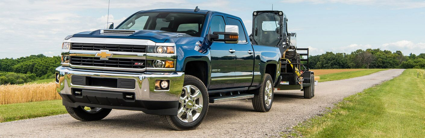 blue 2018 chevrolet silverado 2500hd towing construction equipment on gravel road