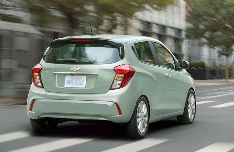 rear view of green 2018 chevrolet spark driving through city street