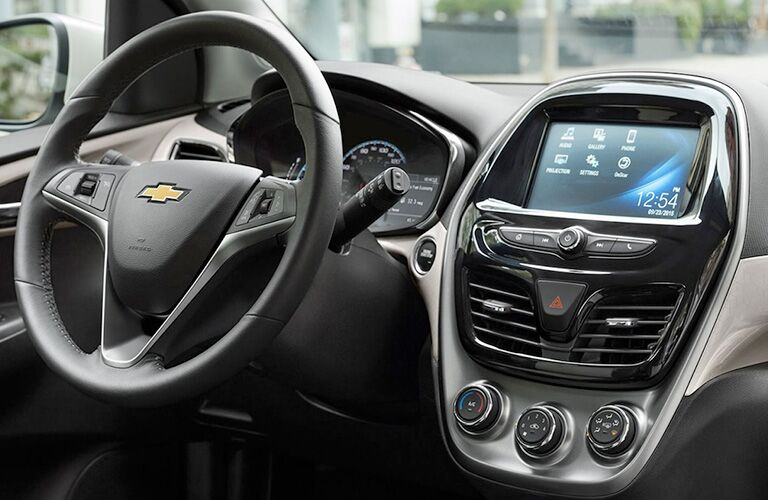 front interior of 2018 chevrolet spark including steering wheel and infotainment system interface