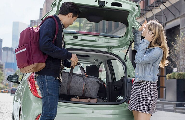 man and woman loading luggage into cargo area of green 2018 chevy spark