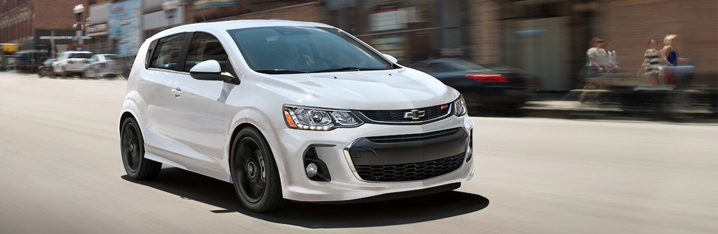 white 2018 chevy sonic driving on city street