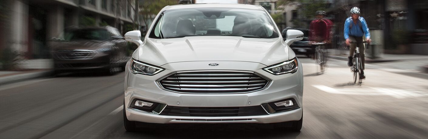 front grille and bumper of white 2018 ford fusion hybrid driving in city