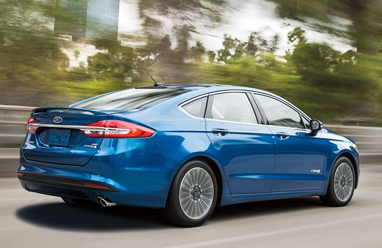 blue 2018 ford fusion hybrid driving on highway