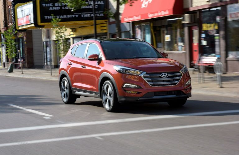 red 2018 hyundai tucson driving through downtown intersection