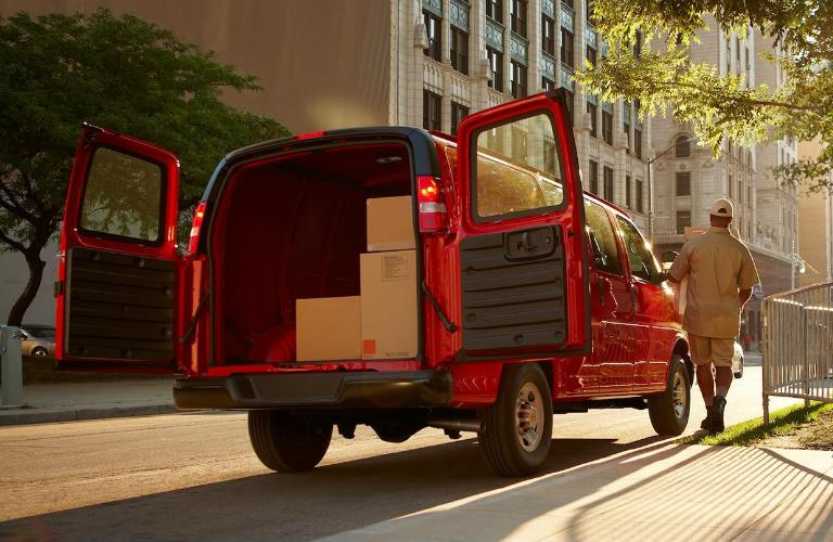 rear view of red 2018 chevrolet express cargo van with doors open and full of boxes